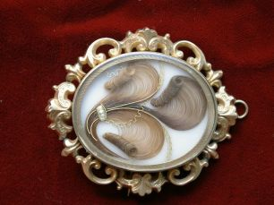 A brooch made of hair in a metal and glass case.